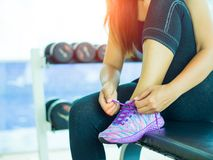 Closeup of woman tying shoe laces. Female sport fitness runner getting ready for jogging in gym room. Running shoes - closeup of woman tying shoe laces. Female stock photos