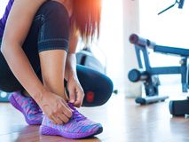 Closeup of woman tying shoe laces. Female sport fitness runner getting ready for jogging in gym room. Running shoes - closeup of woman tying shoe laces. Female stock photo