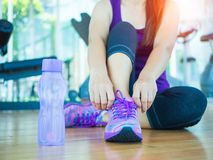 Closeup of woman tying shoe laces. Female sport fitness runner getting ready for jogging. Running shoes - closeup of woman tying shoe laces. Female sport fitness royalty free stock images