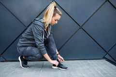 Running shoes - closeup of woman tying shoe laces. Female sport fitness runner getting ready for jogging outdoors royalty free stock photography