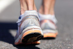 Running shoes feet closeup man jogging on road. Running shoe closeup of man running on road with sports shoes. Road to success. Runner training cardio exercising Royalty Free Stock Images
