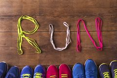 Running shoes on the floor. Five pairs of running shoes and shoelaces run sign on a wooden floor background Stock Photography