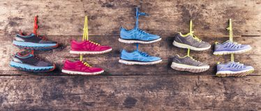Running shoes on the floor. Five pairs of various running shoes hang on a nail on a wooden fence background Royalty Free Stock Images