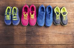 Running shoes on the floor. Four pairs of various running shoes laid on a wooden floor background stock image