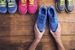 Running shoes on the floor. Four pairs of various running shoes laid on a wooden floor background Stock Photo