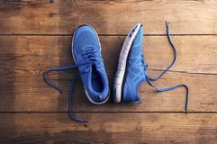 Running shoes on the floor. Pair of blue running shoes laid on a wooden floor background stock photos