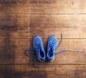 Running shoes on the floor. Pair of blue running shoes laid on a wooden floor background Royalty Free Stock Photos