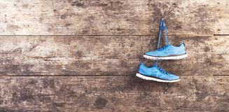 Running shoes on the floor. Pair of running shoes hang on a nail on a wooden fence background Stock Photography