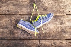 Running shoes on the floor. Pair of running shoes hang on a nail on a wooden fence background Royalty Free Stock Photo