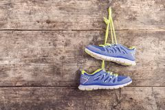 Running shoes on the floor. Pair of running shoes hang on a nail on a wooden fence background stock image