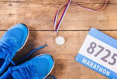 Running shoes on the floor. Pair of running shoes, medal and race number on a wooden floor background Royalty Free Stock Photo