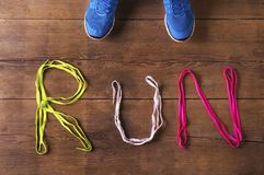 Running shoes on the floor. Pair of running shoes and shoelaces run sign on a wooden floor background Royalty Free Stock Photos