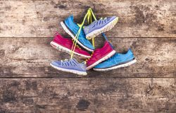 Running shoes on the floor. Three pairs of running shoes hang on a nail on a wooden fence background Stock Photo