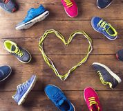 Running shoes on the floor. Various running shoes laid on a wooden floor background Stock Image