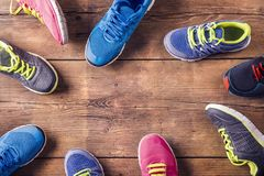 Running shoes on the floor. Various running shoes laid on a wooden floor background Royalty Free Stock Images