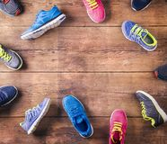 Running shoes on the floor. Various running shoes laid on a wooden floor background Royalty Free Stock Image