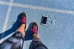 Running shoes girl feet selfie on run track lane. Running shoes girl feet selfie on blue track lane getting ready to run with smartphone and earbuds to listen to royalty free stock image