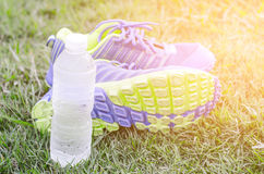 Running shoes on a green grass field and a bottle of water Royalty Free Stock Photos