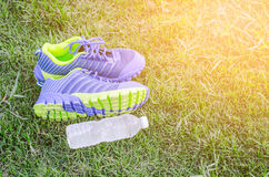Running shoes on a green grass field and a bottle of water Stock Images