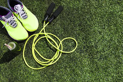 Running shoes, jump rope and drink bottle with green juice Stock Images