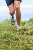 Running shoes and legs of runner jogging outdoors Stock Images