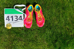 Running shoes,  marathon race bib (number) and finisher medal on grass background, Stock Image