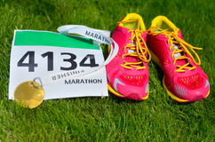 Running shoes,  marathon race bib (number) and finisher medal on grass background,. Sport, fitness and healthy lifestyle concept Stock Photos