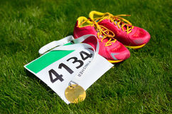 Running shoes,  marathon race bib (number) and finisher medal on grass background, Royalty Free Stock Images