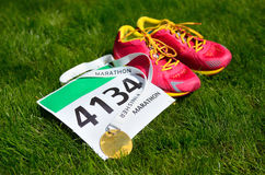 Running shoes,  marathon race bib (number) and finisher medal on grass background, Stock Photo