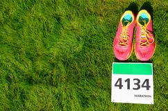 Running shoes and marathon race bib number on grass background, sport, fitness and healthy lifestyle Stock Photos