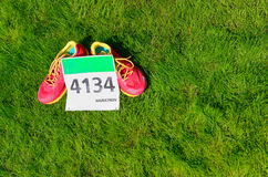 Running shoes and marathon race bib (number) on grass background, sport, fitness and healthy lifestyle. Concept Royalty Free Stock Photos