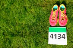 Running shoes and marathon race bib number on grass background, sport, fitness and healthy lifestyle Royalty Free Stock Images