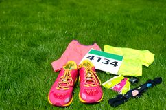 Running shoes, marathon race bib number, runner gear and energy gels on grass background, sport competition, fitness Stock Photography