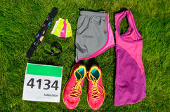 Running shoes, marathon race bib (number), runners gear and energy gels on grass background Stock Photography