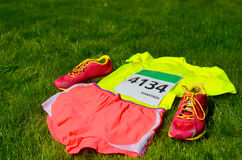 Running shoes, marathon race bib (number), runners gear and energy gels on grass background Stock Images