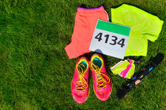 Running shoes, marathon race bib (number), runners gear and energy gels on grass background Royalty Free Stock Photo