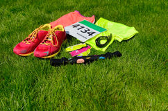 Running shoes, marathon race bib (number), runners gear and energy gels on grass background. Sport, fitness and healthy lifestyle concept Stock Photos
