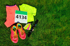 Running shoes, marathon race bib number, runners gear and energy gels on grass background, sport, fitness Royalty Free Stock Photography