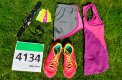 Running shoes, marathon race bib number, runners gear and energy gels on grass background, sport, fitness Stock Image