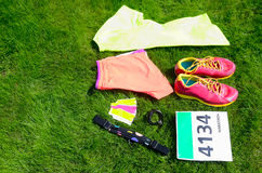 Running shoes, marathon race bib number, runners gear and energy gels on grass background, sport, fitness Royalty Free Stock Images