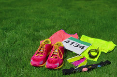 Running shoes, marathon race bib number, runners gear and energy gels on grass background, sport, fitness Royalty Free Stock Photo