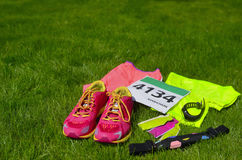 Running shoes, marathon race bib number, runners gear and energy gels on grass background, sport, fitness Stock Images