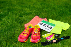 Running shoes, marathon race bib number, runners gear and energy gels on grass background, sport, fitness and healthy lifestyle Stock Photos