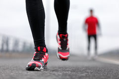 Running shoes of men athletes runners in winter. Running shoes - closeup of male runners running on winter street. Sport fitness athlete man jogging outdoors on stock photos