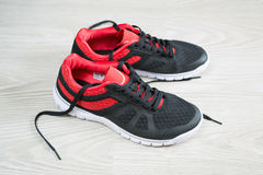 Running shoes with red trim flat on  floor Stock Images