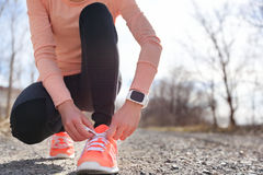 Running shoes and runner sports smartwatch. Female runner tying shoe laces on running trail using smart watch heart rate monitor Royalty Free Stock Image