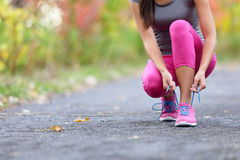 Running shoes woman runner tying shoe lace for run. Closeup of girl getting ready for jogging lacing sport shoe laces. Female sport fitness runner outdoors on royalty free stock photos