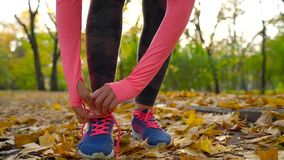 Running shoes - woman tying shoe laces in autumn park at sunset. Slow motion. Running shoes - woman tying shoe laces in autumn park at sunset. Closeup of female stock footage