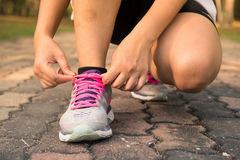 Running shoes - woman tying shoe laces. Closeup of female sport fitness runner getting ready for jogging outdoors on forest. Stock Images