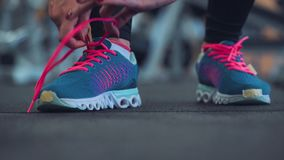 Running shoes - woman tying shoe laces in the gym. Running shoes - woman tying shoe laces. Closeup of fitness woman getting ready for engage in the gym stock footage
